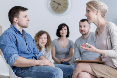 man sitting in group therapy and listening to the psychologist with concerned family in the background